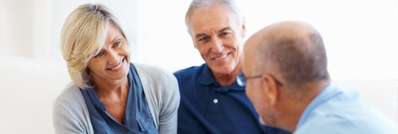 Smiling married couple discussing their retirement plan with a trusted financial advisor.